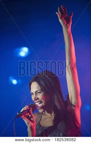 Mixed race woman singing with arm raised