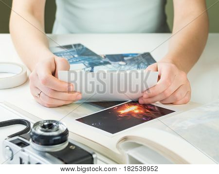 Looking at vintage printed family photos. Young engaged or married female person sitting at white desk holds photograph and chooses pictures for family photo album