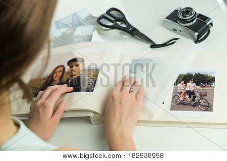 Looking at family wedding photo album. Young female engaged or married person turns pages and selects images for photo album