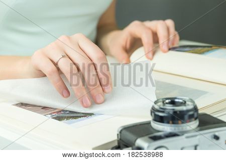 Hand with engagement ring turns page of family photo album. Young female married or engaged person looks at wedding album