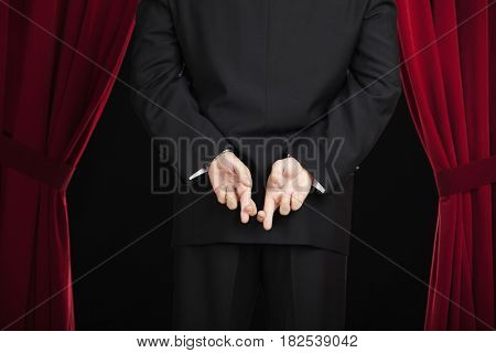 Hispanic man in tuxedo standing backstage with fingers crossed