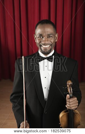 African American man in tuxedo posing onstage with violin