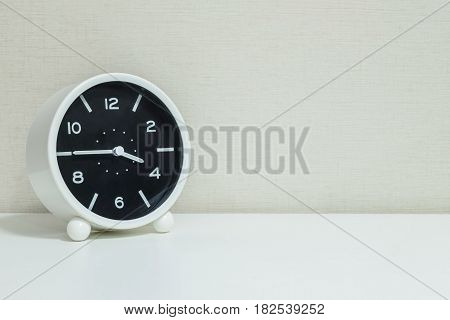 Closeup black and white alarm clock for decorate in a quarter to four o'clock or 3:45 p.m. on white wood desk and cream wallpaper textured background with copy space