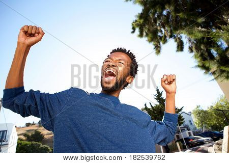 Ecstatic Handsome Man Celebrating With Arms Outstretched