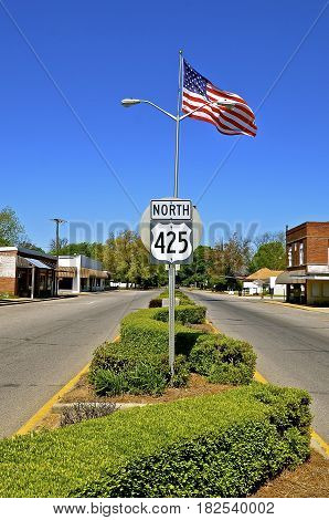 A small rural town with a split Main Street and an American flag  in the median
