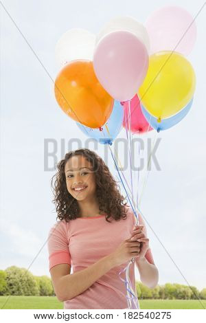 Mixed race teenage girl holding bunch of balloons