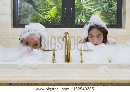 Hispanic teenage girls in bubble bath
