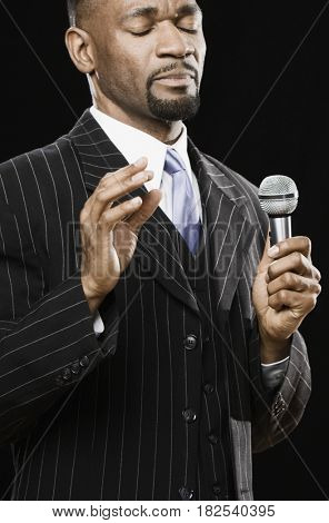African American preacher holding microphone with eyes closed