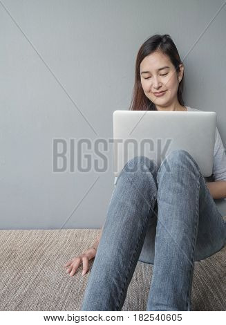 Closeup asian woman sitting for use computer notebook in work concept on blurred cement wall textured background with copy space