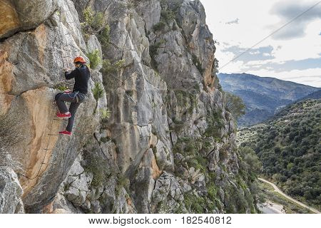 Side view of a woman on a ladderclimbing up to the mountain. Horizontal outdoors shot