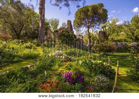 SERMONETA, ITALY - APRIL 16, 2016: The romantic garden of Ninfa with ruins and flowers