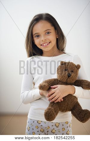 Hispanic girl in pajamas holding teddy bear