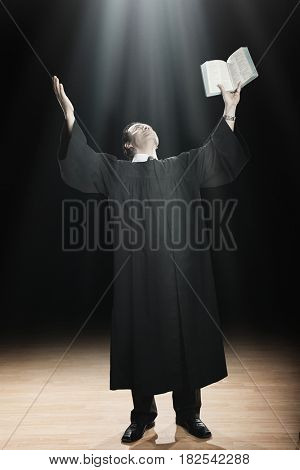 Hispanic priest raising arms to beam of light from ceiling
