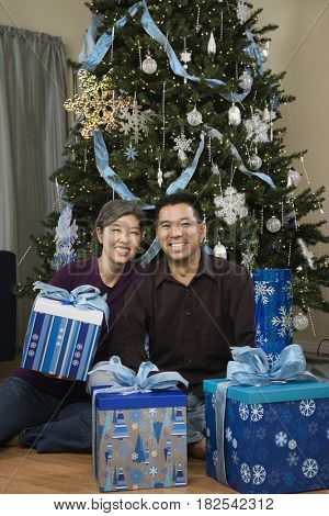Asian couple with Christmas gifts next to tree