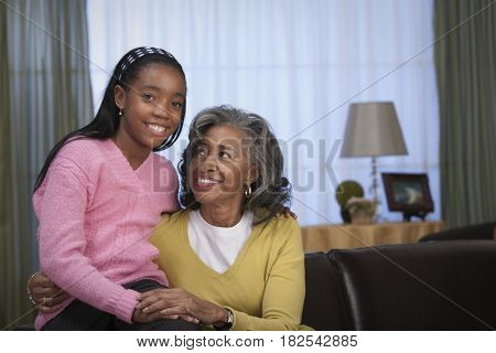 African woman and granddaughter hugging in livingroom