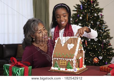 African woman with granddaughter decorating gingerbread house