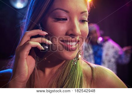 Mixed race woman talking on cell phone in nightclub