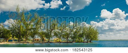Panoramic view of a Caribbean seafront at Water Cay Public Beach  with a playground and wooden colorful hut in Cayman Islands