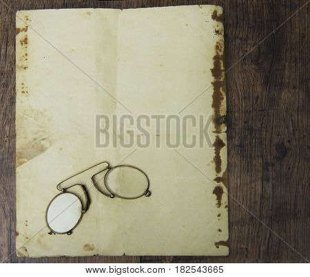 An old pince-nez on old paper, yellow with old age