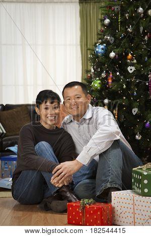 Asian couple next to Christmas tree