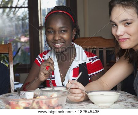 Teenage girls eating fruit salad