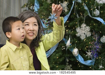 Asian mother and son next to Christmas tree