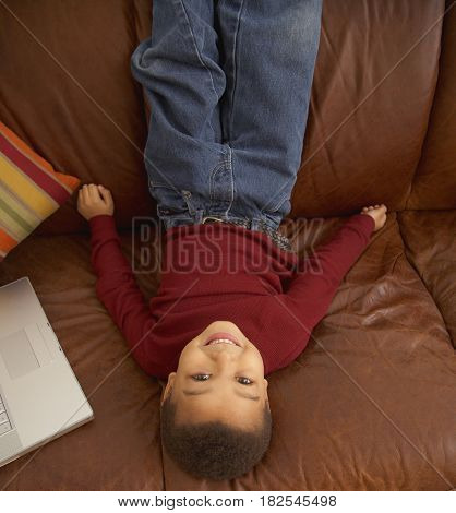 Mixed race boy laying upside down on couch