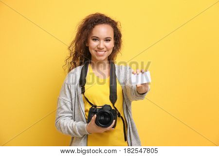 Beautiful African American photographer with business card on color background