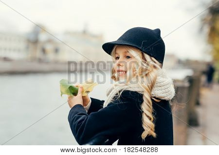 Smiling girl is standing by the river with faded eaves in her hands. She is  wearing black hat and coat.  Background of this image has mild focus