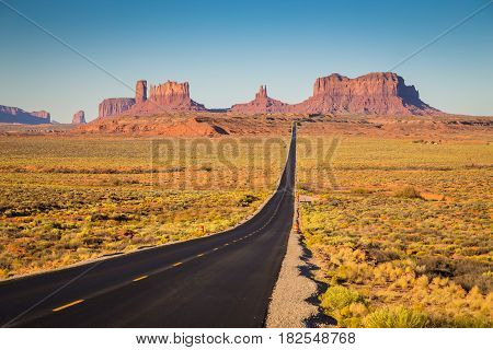 Classic panorama view of historic U.S. Route 163 running through famous Monument Valley in beautiful golden evening light at sunset on a beautiful sunny day with blue sky in summer Utah USA