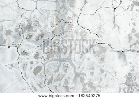 Background of gray crannied wall covered with rough flaking plaster