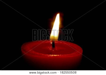 Closeup of a burning red candle in front of black background