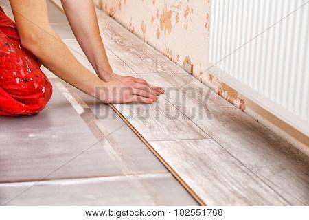 young handyman installing wooden floor in new house hands closeup