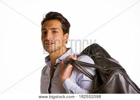 Young attractive man on white background carrying big black leather bag over shoulder