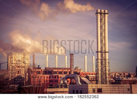 Old coal power plant in the city lit with sunset rays