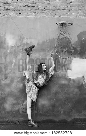 ballerina in a short dress and boots near a concrete wall near a basketball ring. Black and White