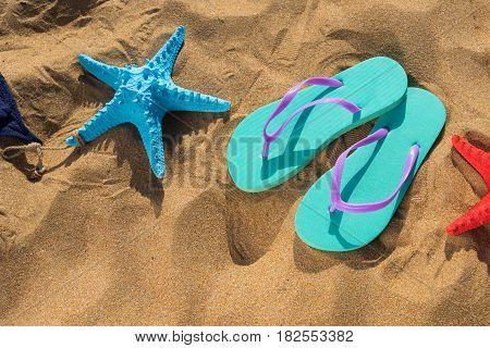 Summer beach fun - sandals with starfish on beach sand