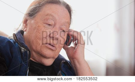 Senior lady - old Woman speak cell telephone, portrait, telephoto