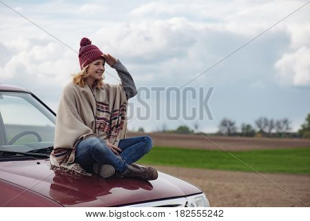 Young adult woman on road trip, watching scenery on off road vehicle