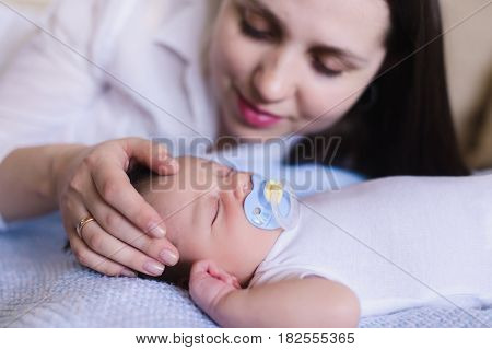 Newborn baby boy with mother. Mom gently stroking the babys head. Baby sweet sleeping on a white bed. Child with a pacifier in his mouth.