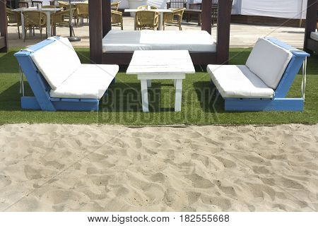 Lounger beds and chair beside the sand beach at relaxing resort south of Spain