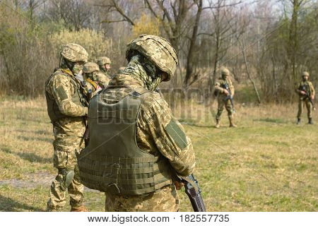 Front Line. Military before attack on battlefield with kalashnikov briefing