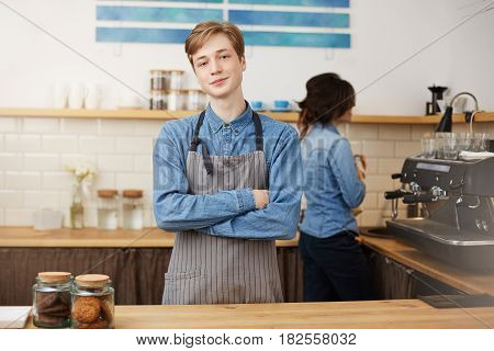 Two young baristas working at bar counter in small coffee house. Male barista looking straight.