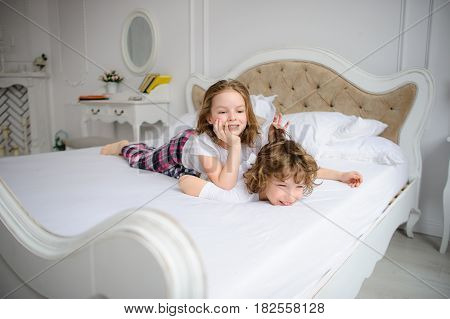 Brother and sister of primary school age play pranks on a bed. Them it is very cheerful.