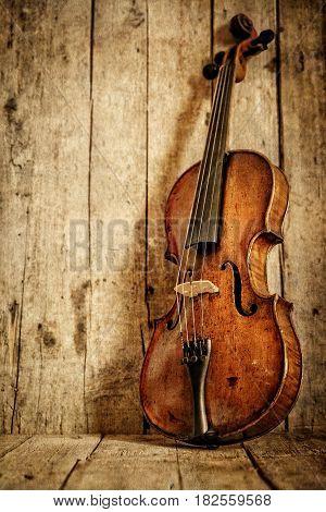 violin in front of wooden background vintage filtered