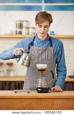 Barista makes pourover coffee pouring water over grounds to extract coffee flavors. Looking focused.