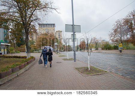 Kiev Ukraine - September 08 2016: Couple under an umbrella on an empty street Institutskaya