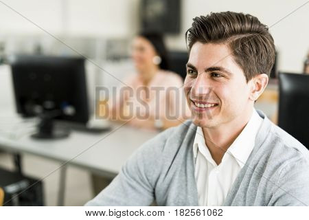Young handsome man studying information technology in a classroom and smiling