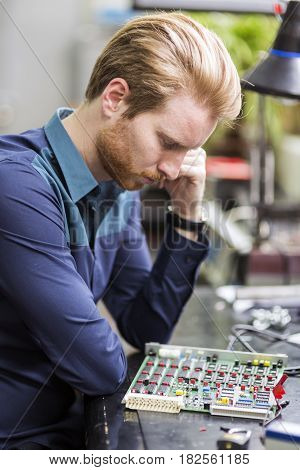 Young handsome man thinking while soldering a circuit board and working on fixing hardware
