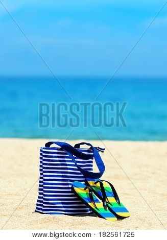 Beach accessories. Concept of summer vacations. Flip-flops and bag.